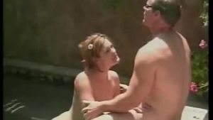 Big titted blonde and her partner are fucking naked next to a swimming pool, just for fun
